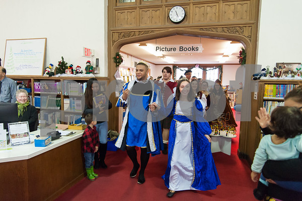 12/12/17 Wesley Bunnell | Staff The New Britain High School Madrigal Singers performed as they walked through the public library on Tuesday morning. Giovanni Cirinna, L, and Cate Keithline, lead the singers as they exit the childrens section.