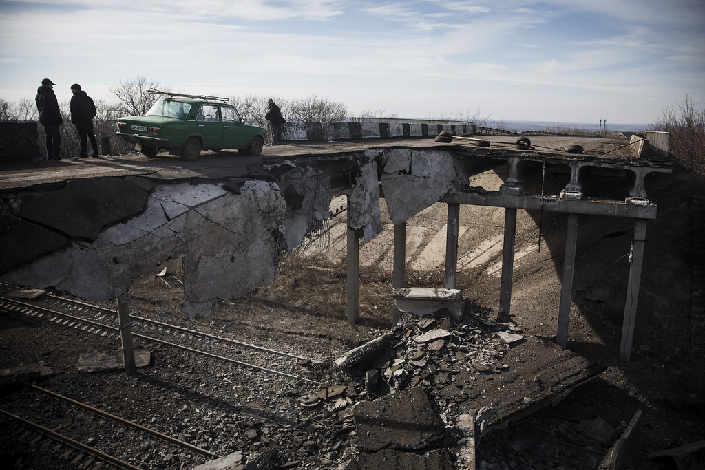 . DEBALTSEVE, UKRAINE - FEBRUARY 25:  A car drives over a partially destroyed bridge on February 25, 2015 in Debaltseve, Ukraine. After approximately one month of fighting, Russian backed rebels successfully forced Ukrainian troops to withdraw from the town on February 18. The town is considered an asset to both Ukrainians and the rebels due to the railway station and it\'s connection to other eastern Ukranian towns.  (Photo by Andrew Burton/Getty Images)