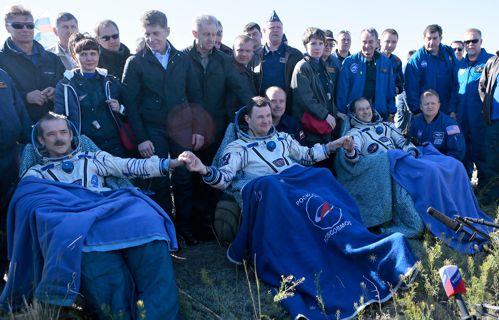 . (Front R-L)  US astronaut Thomas Marshburn, Russian cosmonaut Roman Romanenko, and Canadian astronaut Chris Hadfield join their hands as they rest shortly after the landing aboard the Russian Soyuz space capsule some 150 km (90 miles) southeast of the town of Zhezkazgan in central Kazakhstan on May 14, 2013. AFP PHOTO / POOL /MIKHAIL METZEL/AFP/Getty Images