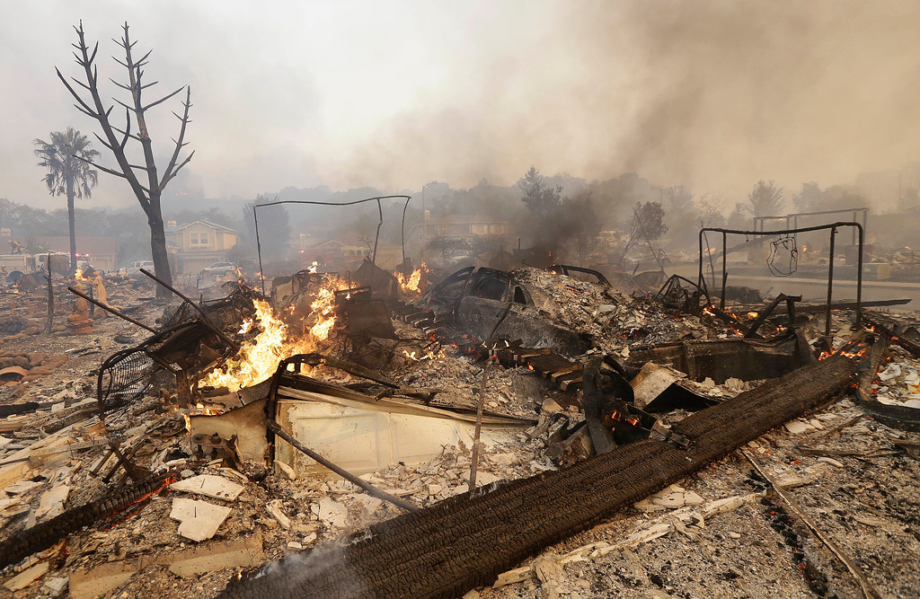 . Flames rise from the remains of a house that burned down in Santa Rosa, Calif., Monday, Oct. 9, 2017. Wildfires whipped by powerful winds swept through Northern California, sending residents on a headlong flight to safety through smoke and flames as homes burned. (AP Photo/Jeff Chiu)
