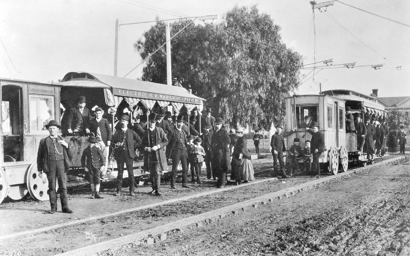 Portrait of passengers, conductors and engineers posing near Pico Boulevard Electric Railroad cars, Los Angeles, 1887