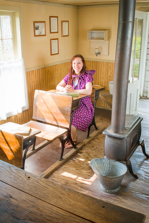Becky sits at a desk next to the pot-belly stove inside the schoolhouse.