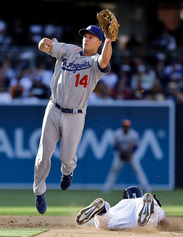 . Los Angeles Dodgers second baseman Mark Ellis (14) leaps high to snare a wild throw as San Diego Padres\' Will Venable steals second during the fifth inning of a baseball game in San Diego, Tuesday, April 9, 2013. (AP Photo/Lenny Ignelzi)