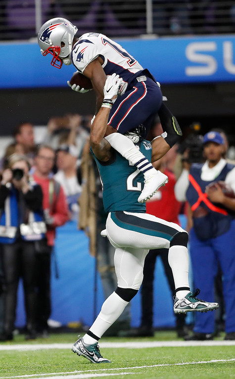. New England Patriots\' Brandin Cooks, top, is stopped by Philadelphia Eagles\' Rodney McLeod during the first half of the NFL Super Bowl 52 football game Sunday, Feb. 4, 2018, in Minneapolis. (AP Photo/Jeff Roberson)