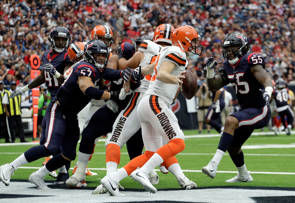 . Cleveland Browns quarterback Kevin Hogan (8) scrambles before being tackled for a safety by Houston Texans linebacker Benardrick McKinney (55) asBrennan Scarlett (57) pursues in the second half of an NFL football game, Sunday, Oct. 15, 2017, in Houston. (AP Photo/Eric Gay)