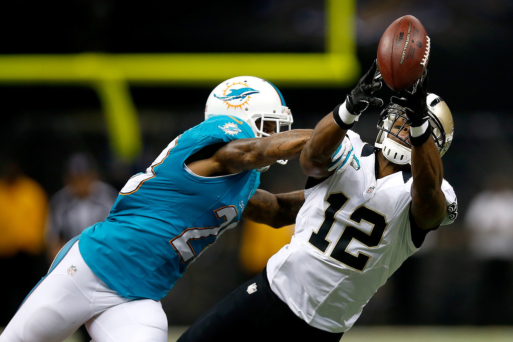 . Cornerback Nolan Carroll #28 of the Miami Dolphins breaks up a pass to wide receiver Marques Colston #12 of the New Orleans Saints in the first half at the Mercedes-Benz Superdome on September 30, 2013 in New Orleans, Louisiana.  (Photo by Chris Graythen/Getty Images)