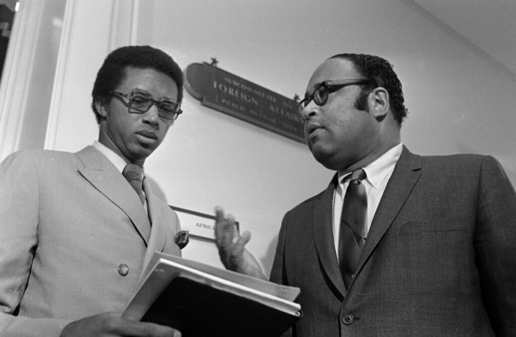 ". Tennis star Arthur Ashe of Richmond, Va., left, talks with Chairman Charles C. Diggs, D-Michigan, of the House Foreign Affairs subcommittee on Africa, Feb. 4, 1970.  Ashe was denied a visa by South Africa, compelling hearings ""to probe the foreign implications of a black American having his visa denied,\"" said Diggs.  (AP Photo/Bob Daugherty)"