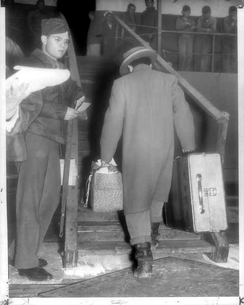 """""""Turning His Back -- At San Pedro yesterday, Harada Teruyoshi (carrying suitcase) was one of 676 Japanese who turned their backs on the United States and boarded the transport General Ernst to sail for Japan.  Many left voluntarily.""""--caption on photograph"""