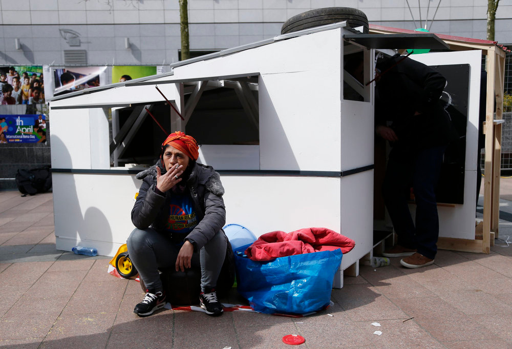 . A woman sits outside a mock makeshift house during a protest against Romani evictions in front of the European Union Parliament to mark the International Roma Day in Brussels on April 8, 2013.  REUTERS/Francois Lenoir