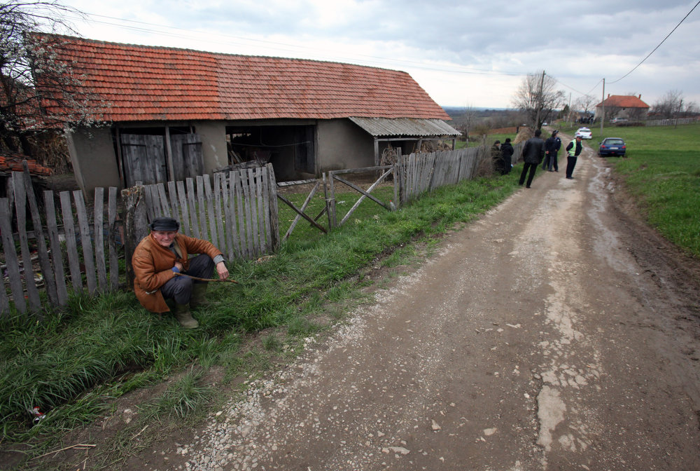 . People wait on the street in the village of Velika Ivanca, Serbia, Tuesday, April 9, 2013. A 60-year-old man gunned down 13 people, including a baby, in a house-to-house rampage in a quiet village on Tuesday before trying to kill himself and his wife, police and hospital officials said. Belgrade emergency hospital spokeswoman Nada Macura said the man, identified as Ljubisa Bogdanovic, used a handgun in the shooting spree at five houses. The dead included six women. (AP Photo/Darko Vojinovic)