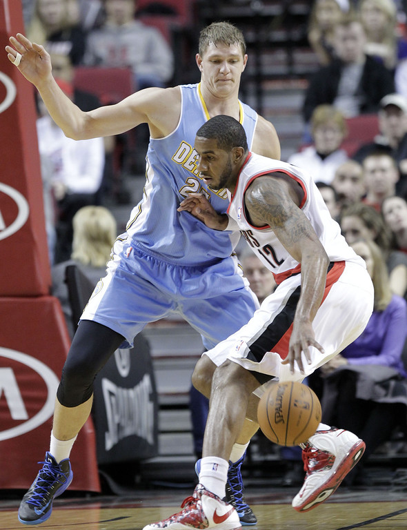 . Portland Trail Blazers forward LaMarcus Aldridge, right, drives against Denver Nuggets center Timofey Mozgov, from Russia, during the first half of an NBA basketball game in Portland, Ore., Saturday, March 1, 2014. (AP Photo/Don Ryan)
