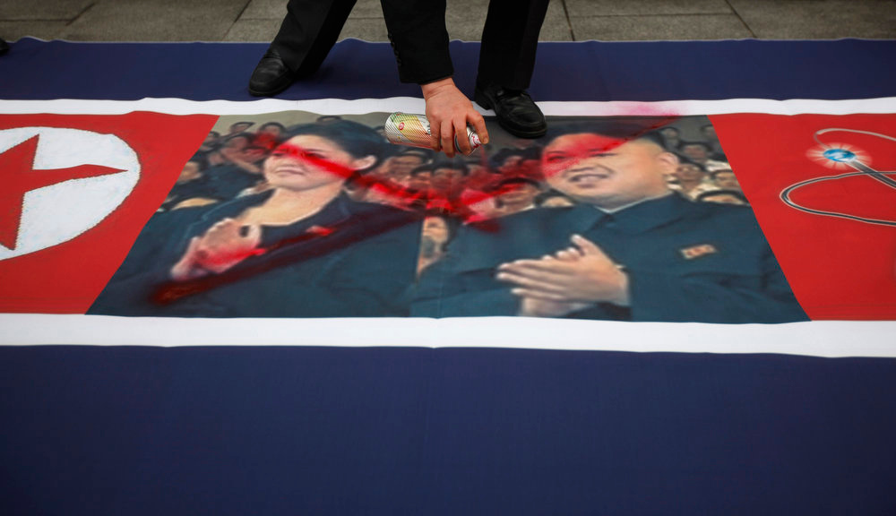 Description of . An activist from an anti-North Korea civic group defaces a North Korea flag depicting North's leader Kim Jong-un (R) and his wife Ri Sol-ju (L) during a rally against North Korea's nuclear test near the U.S. embassy in central Seoul February 12, 2013. North Korea conducted its third-ever nuclear test on Tuesday, a move likely to anger its main ally China and increase international action against Pyongyang and its new young leader, Kim Jong-un. U.N. Secretary-General Ban Ki-moon condemned North Korea's test, saying it was a