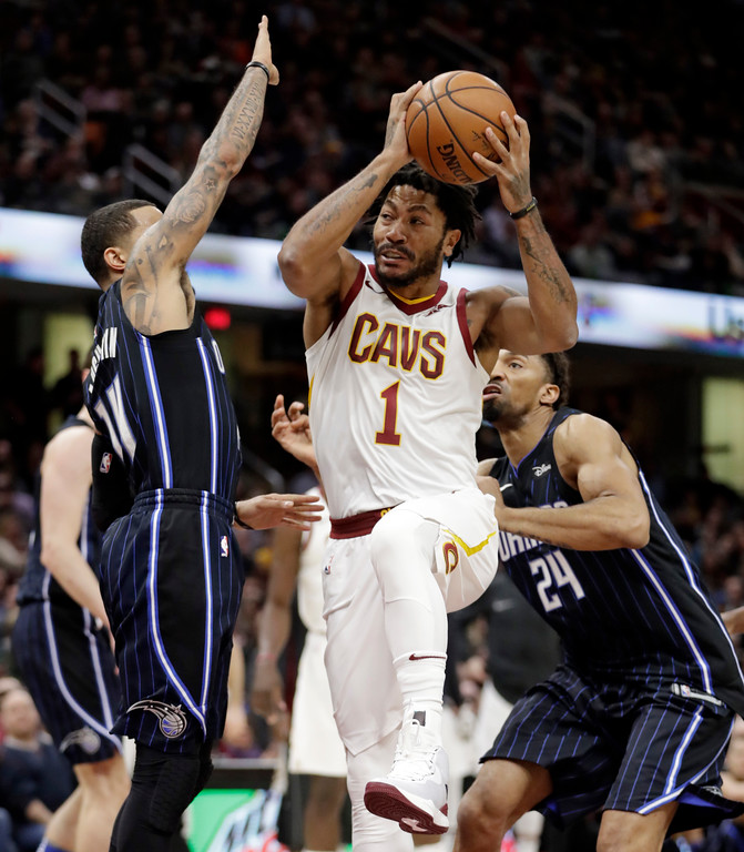 . Cleveland Cavaliers\' Derrick Rose, center, drives between Orlando Magic\'s D.J. Augustin, left, and Khem Birch during the first half of an NBA basketball game Thursday, Jan. 18, 2018, in Cleveland. (AP Photo/Tony Dejak)