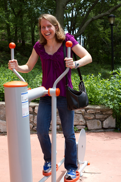 Carrie plays with the exercise equipment on the running path