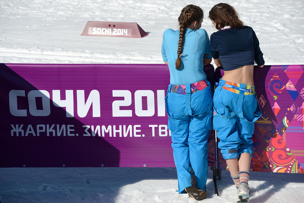. Two volunteers enjoy the sun before the start of the Women\'s Cross-Country Skiing 10km Classic at the Laura Cross-Country and Biathlon Center during the Sochi Winter Olympics February 13, 2014 in Rosa Khutor near Sochi. (KIRILL KUDRYAVTSEV/AFP/Getty Images)