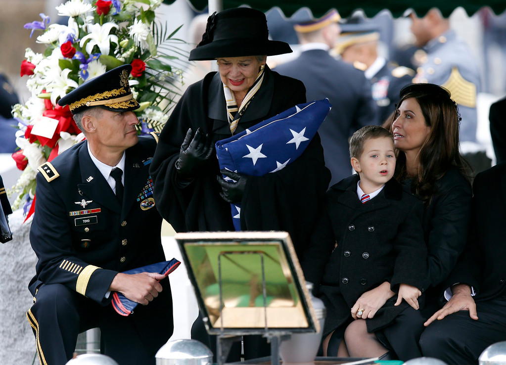 . Brenda Schwarzkopf, widow of the late U.S. Four Star General H. Norman Schwarzkopf, is comforted by U.S. Army Major General Kenneth Tovo (L) at her late husband\'s graveside while holding an American flag at Schwarzkopf\'s burial service at the United States Military Academy at West Point, New York, February 28, 2013.  REUTERS/Mike Segar