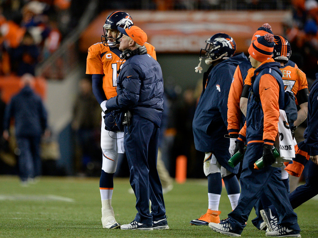 . Denver Broncos quarterback Peyton Manning (18) and  head coach John Fox confer during the fourth quarter. The Denver Broncos vs. The San Diego Chargers in an AFC Divisional Playoff game at Sports Authority Field at Mile High in Denver on January 12, 2014. (Photo by John Leyba/The Denver Post)