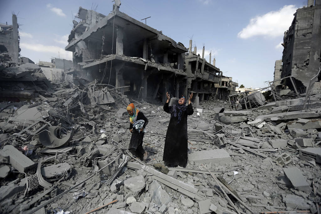 . A Palestinian woman pauses amid destroyed buildings in the northern district of Beit Hanun in the Gaza Strip during an humanitarian truce on July 26, 2014. The bodies of at least another 35 Palestinians were recovered from rubble across Gaza during a truce, raising to over 900 the overall death toll of Israel\'s onslaught on the territory since July 8, medics said. AFP PHOTO / MOHAMMED ABED/AFP/Getty Images