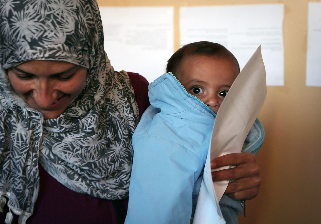 . A Syrian mother and her baby wait for a medical check up in a corridor of a newly opened refugee camp,  in an old school in Sofia, Saturday, Oct. 26, 2013 as volunteers provided medical and food aid to hundreds of refugees . Bulgaria is a gateway to the European Union for refugees fleeing Syria via Turkey, many crossing the border illegally to seek asylum. Bulgaria asked and was promised EU aid to deal with the ongoing refugee influx.   (AP Photo/Valentina Petrova)