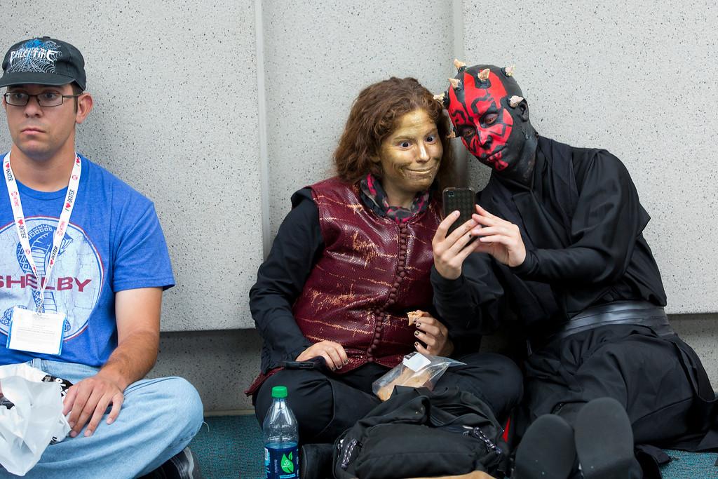 . Alison Tilzer, right, and Lindsay Brzenski, center, enjoy photos from Comic-Con, Friday, July 19, 2013, in San Diego. (AP Photo/U-T San Diego, Nelvin C. Cepeda)
