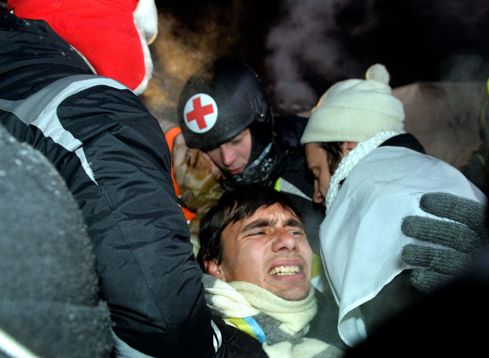 """. People carry a wounded protester during clashes with the riot police on Independence Square in Kiev on December 11, 2013. Ukrainian security forces on December 11 stormed Kiev\'s Independence Square which protesters have occupied for over a week but the demonstrators defiantly refused to leave and resisted the police in a tense standoff. Eite Berkut anti-riot police and interior ministry special forces moved against the protestors at around 2:00 am (midnight GMT) in a move that prompted US Secretary of State John Kerry to express \""""disgust\"""" over the crackdown. SERGEI SUPINSKY/AFP/Getty Images"""