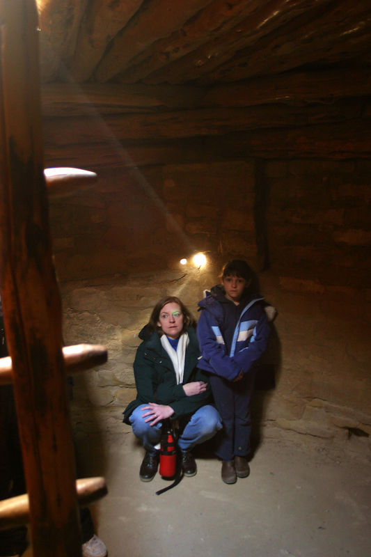 Linda and Anisa lit up by a ray of sunlight in the underground shelter.