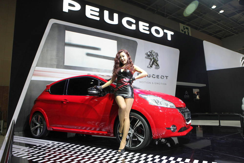 . South Korean models pose with Peugeot 208 GTi during a press day of the Seoul Motor Show in Goyang, South Korea, Thursday, March 28, 2013. The exhibition, with 384 companies from 14 countries to participate, will be held from March 29 through April 7. (AP Photo/Ahn Young-joon)
