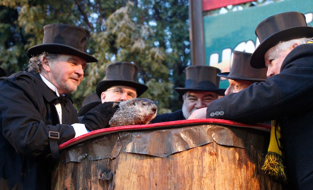. Groundhog Club President Bill Deeley, right, looks and listens to Punxsutawney Phil,  the weather predicting groundhog, as handler John Griffiths, left, awaits the prediction that winter has ended on Groundhog Day, Wednesday, Feb. 2, 2011, in Punxsutawney, Pa. (AP Photo/Keith Srakocic)