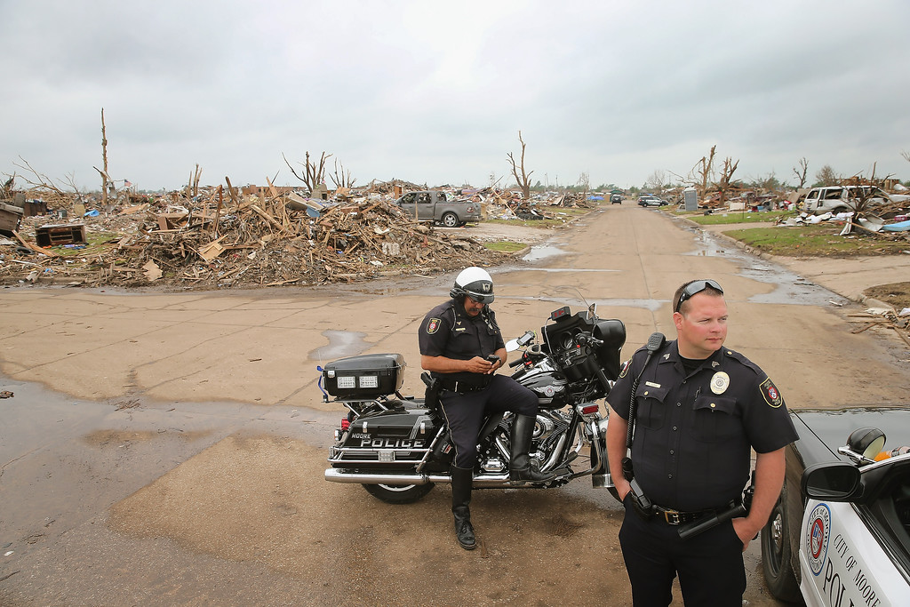 . Police officers block residents and volunteers from getting to homes near the Plaza Towers Elementary School because the area has been secured for a visit by President Barack Obama on May 26, 2013 in Moore, Oklahoma. A tornado hit Moore on May 20, killing at least 24 people and destroying hundreds of homes and businesses.  (Photo by Scott Olson/Getty Images)
