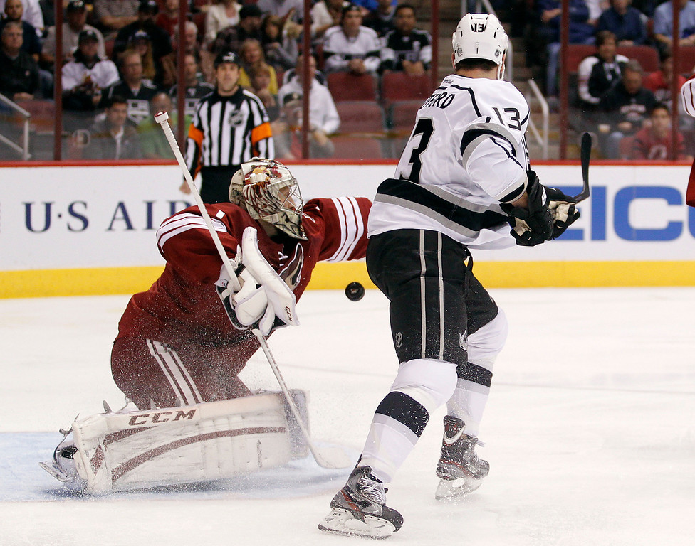 . Los Angeles Kings left winger Kyle Clifford, right, tips a shot past Phoenix Coyotes goalie Jason LaBarbera, left, but wide of the net in the first period of an NHL hockey game Tuesday, April 2, 2013, in Glendale, Ariz. (AP Photo/Paul Connors)