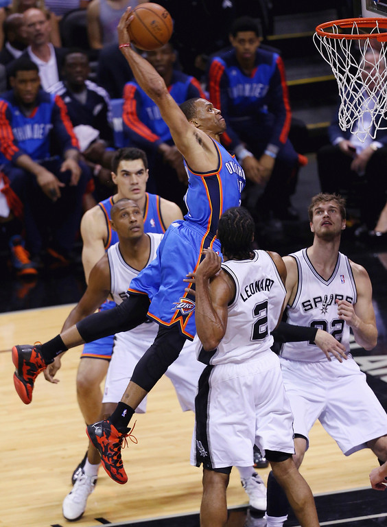 . Russell Westbrook #0 of the Oklahoma City Thunder goes up for a dunk against Kawhi Leonard #2 of the San Antonio Spurs in the first quarter during Game Five of the Western Conference Finals of the 2014 NBA Playoffs at AT&T Center on May 29, 2014 in San Antonio, Texas.   (Photo by Chris Covatta/Getty Images)