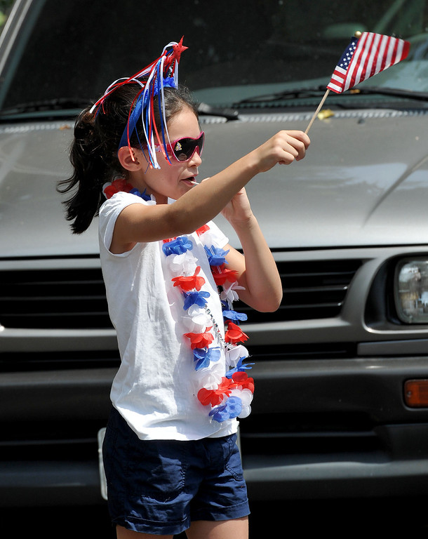 . (John Valenzuela/Staff Photographer)  Isabela Lopez-Davis 7, of Yucaipa waves her American flag during the 2013 Redlands Fourth of July Parade at Sylvan Park, July 4, 2013.