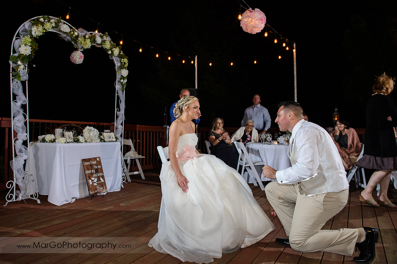 groom kneeling in front of bride sitting on the chair during backyard wedding reception