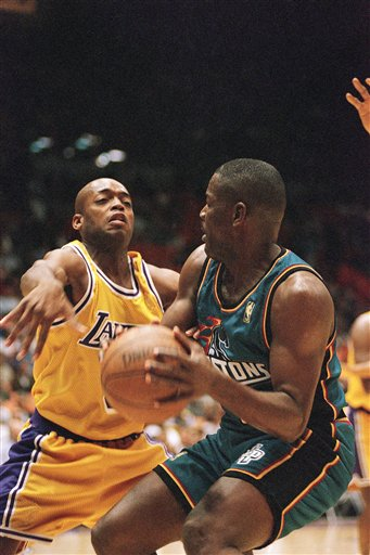 Description of . The Los Angeles Lakers? Nick Van Exel, left, attempts to swat a ball away from the Detroit Pistons? Joe Dumars during their game at the Forum in Inglewood, Calif., on Saturday, Jan. 18, 1997. (AP Photo/Michael Caulfield)