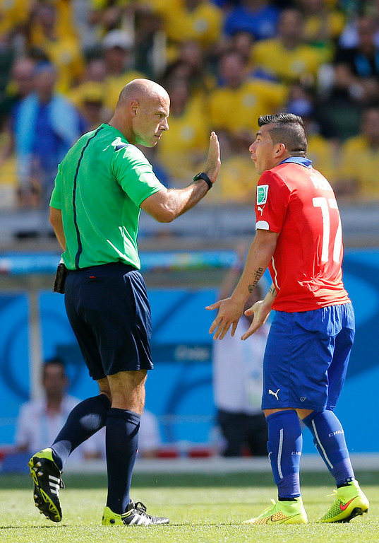 . Referee Howard Webb speaks with Chile\'s Gary Medel during the World Cup round of 16 soccer match between Brazil and Chile at the Mineirao Stadium in Belo Horizonte, Brazil, Saturday, June 28, 2014. (AP Photo/Frank Augstein)
