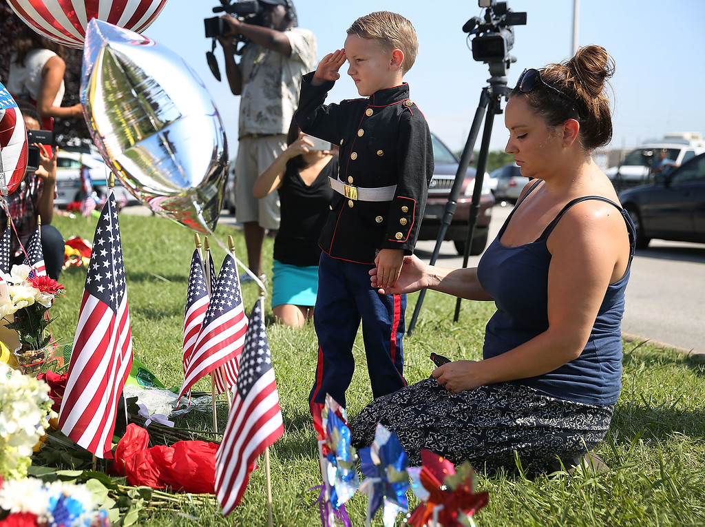 . Blake Miller and his mother, Ashley Miller whose husband is a Lieutenant in the Marine Corps pay their respects to those killed while visiting a memorial placed in front of the Armed Forces Career Center/National Guard Recruitment Office which had been shot up on July 17, 2015 in Chattanooga, Tennessee. According to reports, Mohammod Youssuf Abdulazeez, 24, opened fire on the military recruiting station at the strip mall and then drove to an operational support center operated by the U.S. Navy more than seven miles away and killed four United States Marines there.  (Photo by Joe Raedle/Getty Images)