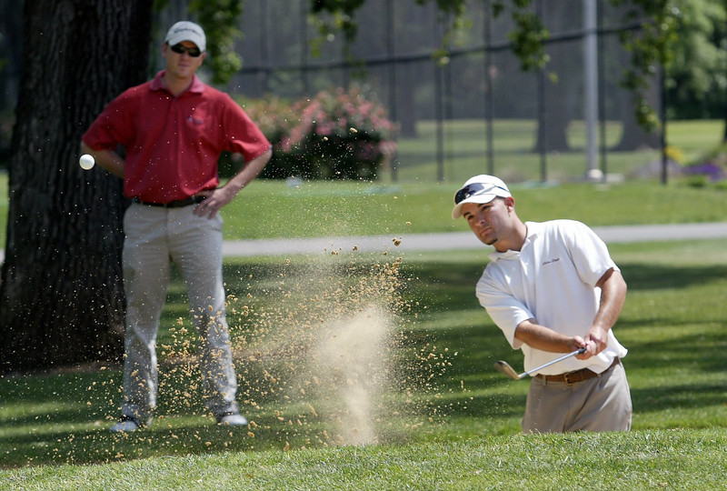 Chico State golf coach Kieth Thomas watches golfer Chris Massoletti knock a ball out of the sand at the practice putting green at Butte Creek Golf Course Friday afternoon. - Halley photo 4/29/05