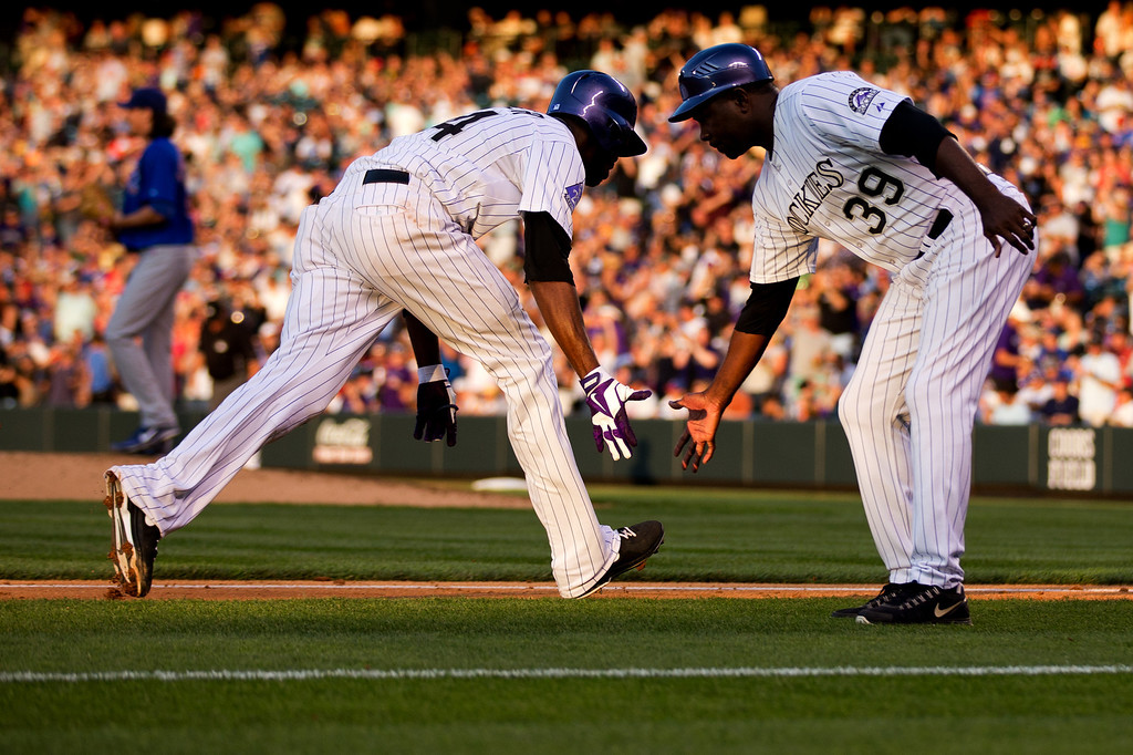 . DENVER, CO - JULY 19:  Dexter Fowler #24 of the Colorado Rockies celebrates with third base coach Stu Cole #39 after hitting a solo home run off of Jeff Samardzija #29 of the Chicago Cubs during the fourth inning at Coors Field on July 19, 2013 in Denver, Colorado.  (Photo by Justin Edmonds/Getty Images)