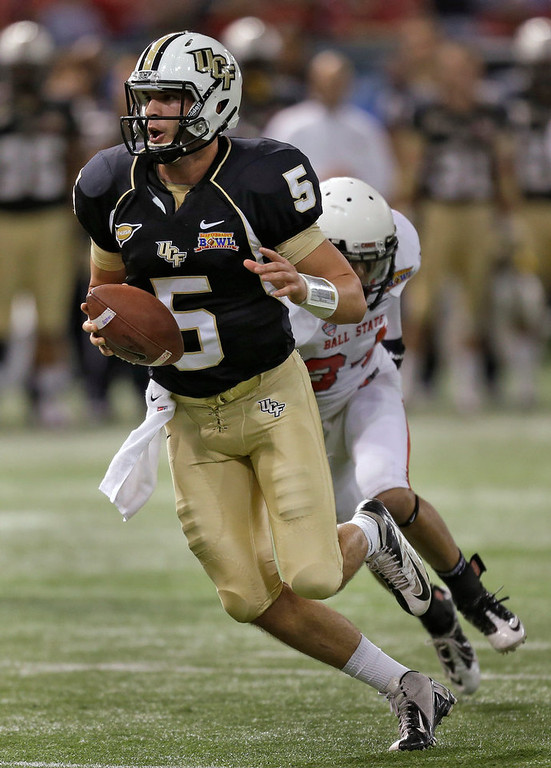 . Central Florida quarterback Blake Bortles (5) eludes Ball State safety Jarrett Swaby (34) on a run during the first quarter of the Beef \'O\' Brady\'s Bowl NCAA college football game Friday, Dec. 21, 2012, in St Petersburg, Fla. (AP Photo/Chris O\'Meara)
