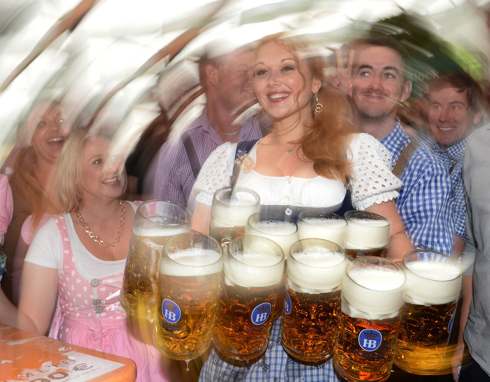 . A waitress serves beer mugs during the opening of the Oktoberfest beer festival at the Theresienwiese in Munich, southern Germany, on September 21, 2013. The world\'s biggest beer festival Oktoberfest will run until October 6, 2013.  AFP PHOTO / CHRISTOF  STACHE/AFP/Getty Images