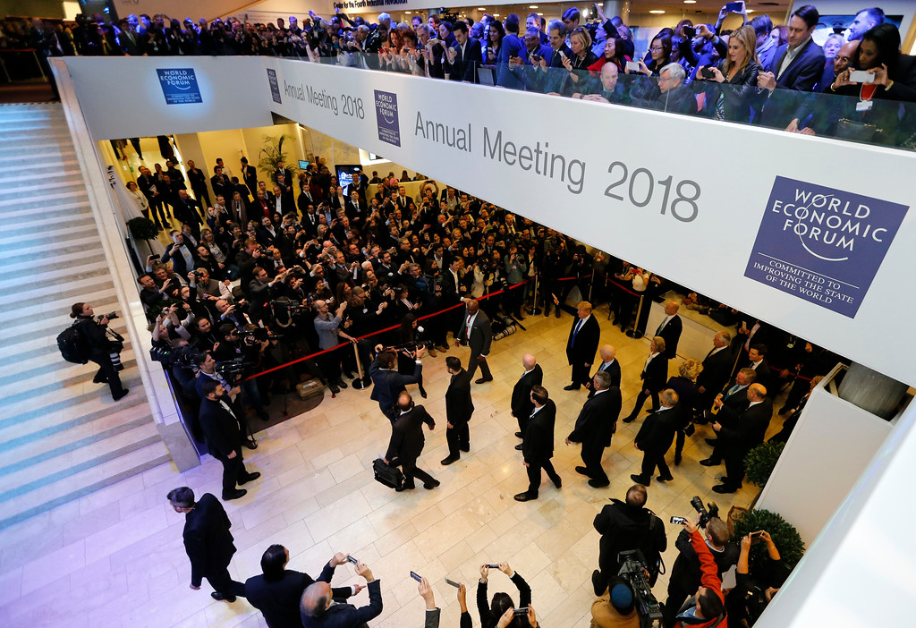 . U.S. President Donald Trump, center right, waves as he arrives during the annual meeting of the World Economic Forum in Davos, Switzerland, Thursday, Jan. 25, 2018. (AP Photo/Michael Probst)