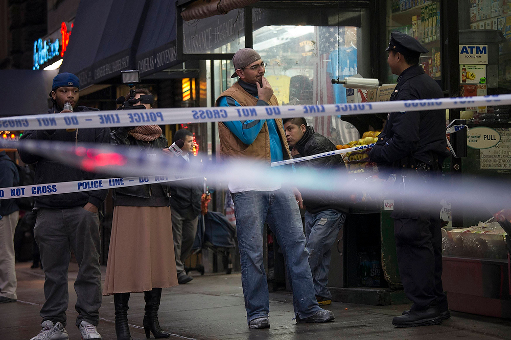 . A pedestrian tries to talk his way past a police cordon near the site of shooting in Manhattan, New York December 10, 2012. New York City police are looking for a suspect after a person was shot in the head in Manhattan, local media reported.  REUTERS/Adrees Latif