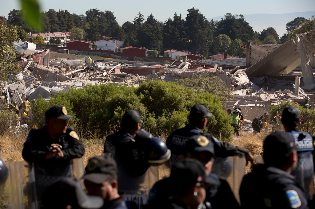 . Police guard the entrance to the area where rescue workers combed through the rubble of a children\'s hospital after a gas truck exploded, in Cuajimalpa on the outskirts of Mexico City, Thursday, Jan. 29, 2015. (AP Photo/Rebecca Blackwell)