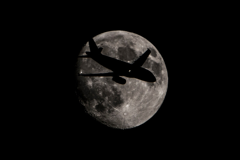 Airplane Silhouetted Moon