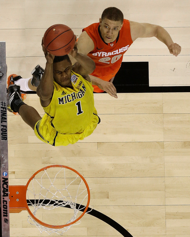 . Michigan\'s Glenn Robinson III (1) heads to the hoop as Syracuse\'s Brandon Triche (20) defends during the second half of the NCAA Final Four tournament college basketball semifinal game Saturday, April 6, 2013, in Atlanta. (AP Photo/Charlie Neibergall)