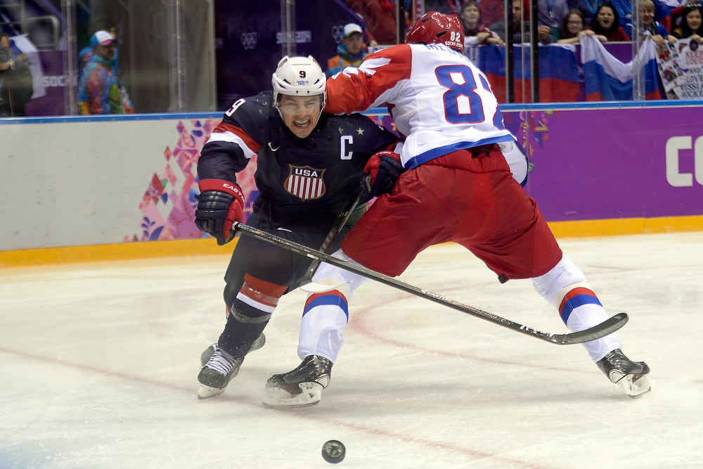 . Yevgeni Medvedev (82) of the Russia defends Zach Parise (9) of the U.S.A. during the first period of men\'s hockey action at Bolshoy arena. Sochi 2014 Winter Olympics on Saturday, February 15, 2014. (Photo by AAron Ontiveroz/The Denver Post)