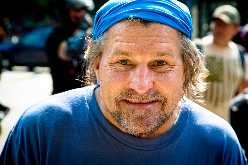 """A man wearing a blue bandana on his head looks into my camera. He was marching with the supporters of the """"Liberty or Death"""" rally."""