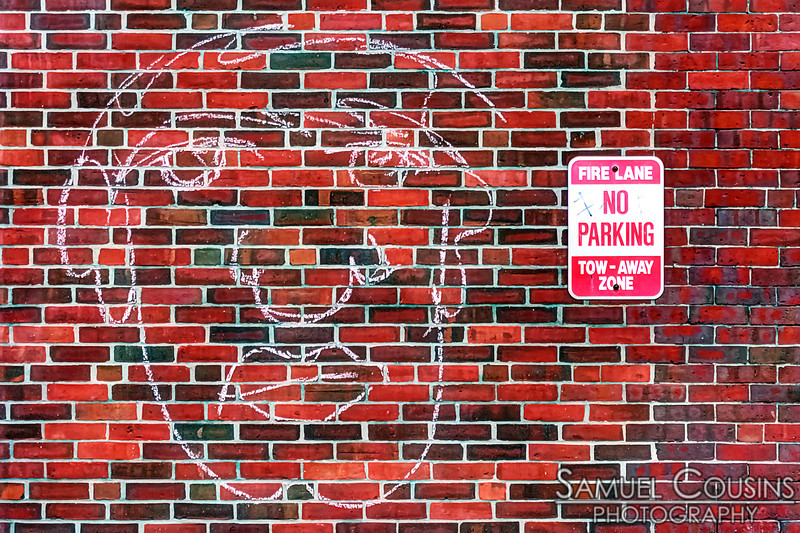 A chalk-drawing of a face on a brick wall.