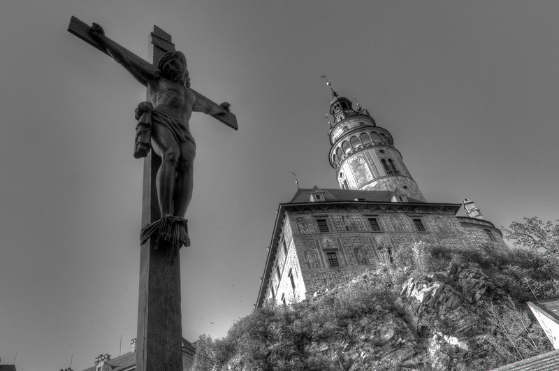 Crucified Jesus on cross with Castle Tower in the background - Cesky Krumlov, Czech Republic