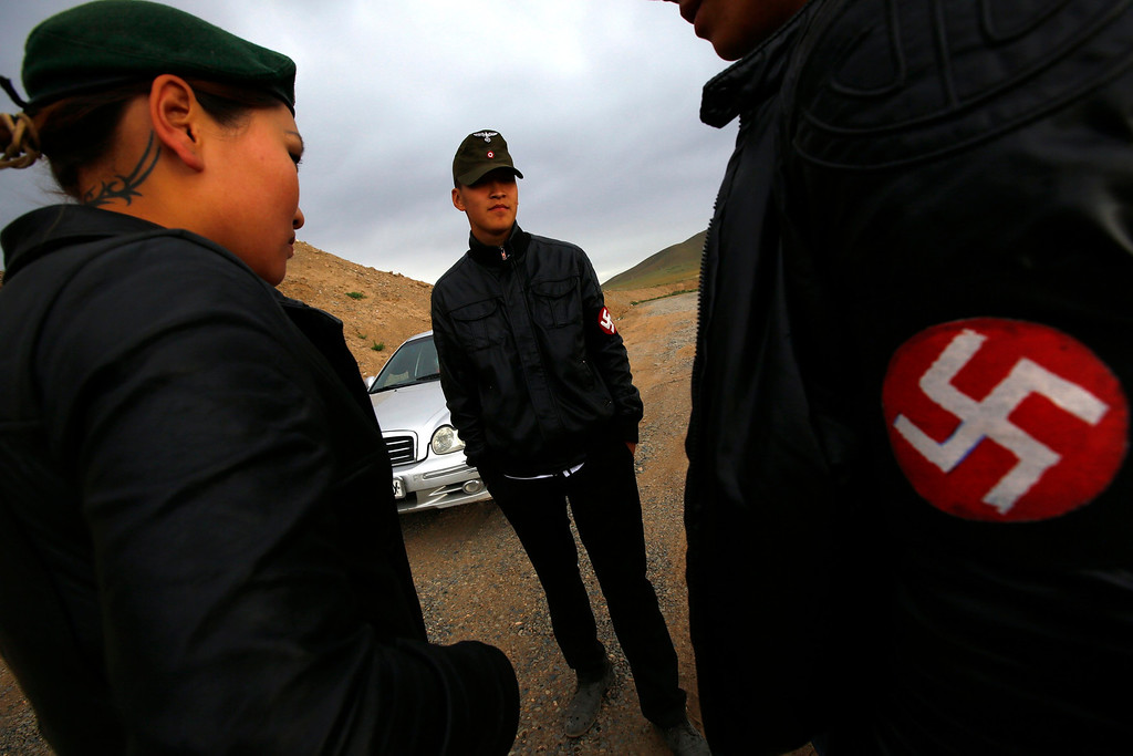 . Members of the Mongolian neo-Nazi group Tsagaan Khass stand near a quarry, where they questioned a worker, southwest of Ulan Bator June 23, 2013. The group has rebranded itself as an environmentalist organisation fighting pollution by foreign-owned mines, seeking legitimacy as it sends Swastika-wearing members to check mining permits. Over the past years, ultra-nationalist groups have expanded in the country and among those garnering attention is Tsagaan Khass, which has recently shifted its focus from activities such as attacks on women it accuses of consorting with foreign men to environmental issues, with the stated goal of protecting Mongolia from foreign mining interests. This ultra-nationalist group was founded in the 1990s and currently has 100-plus members. Picture taken June 23, 2013. REUTERS/Carlos Barria